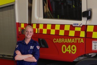 A smiling Kaitlyn in uniform standing next to Cabramatta fire truck 049.