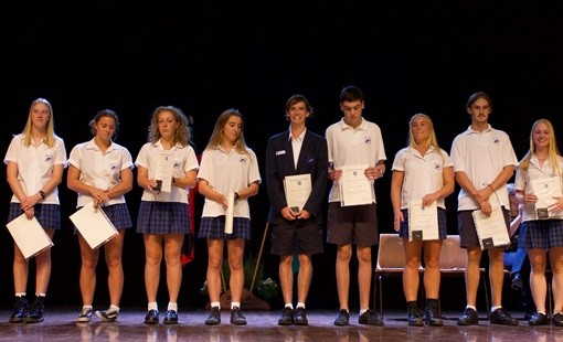 Students on stage with their awards